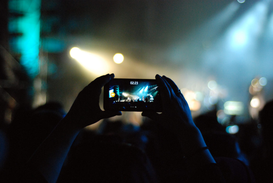 Person films concert with cell phone