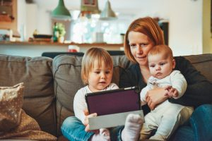 Woman and children watching electronic device
