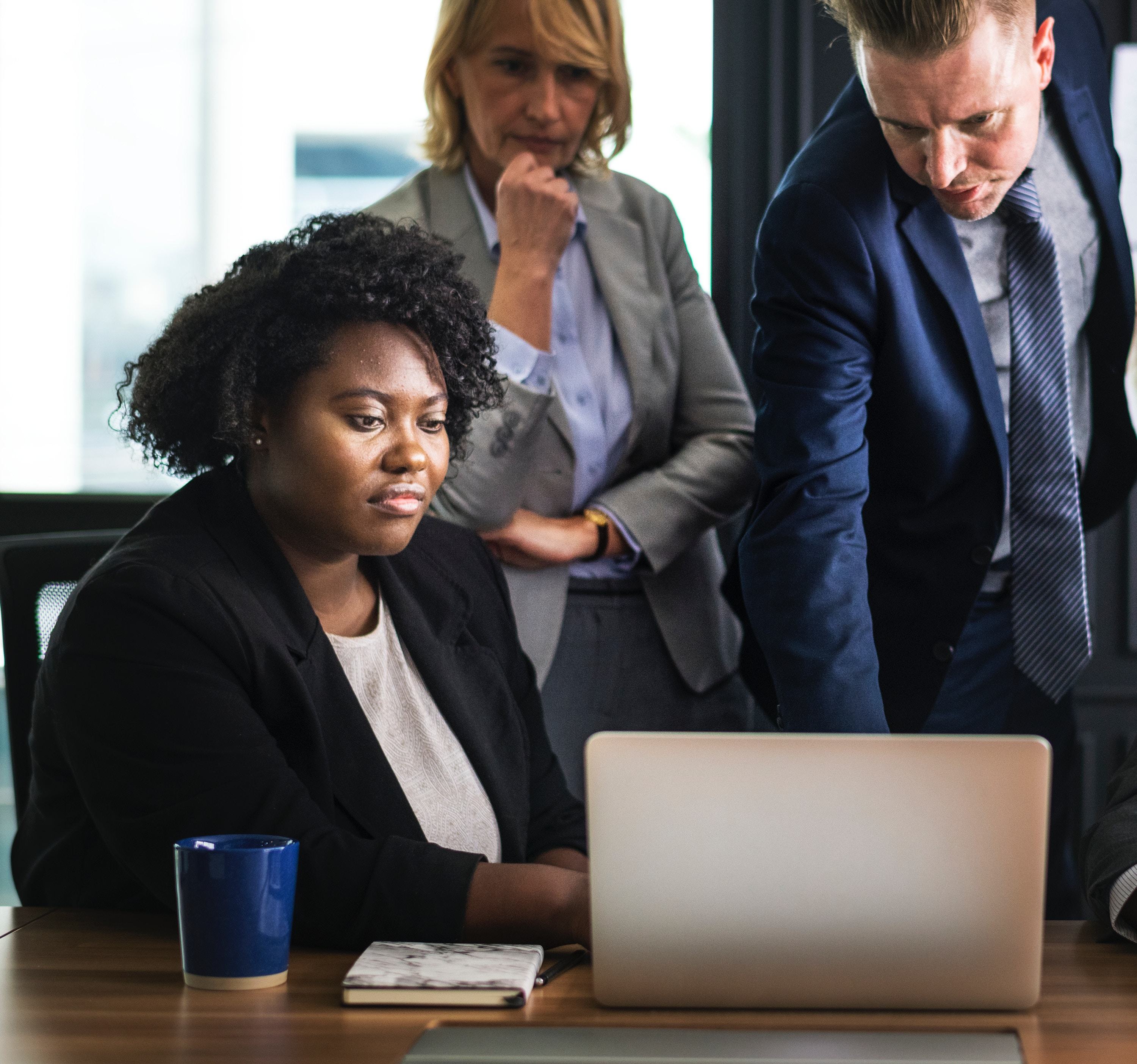 Three people in business suits look at a laptop screen on a desk