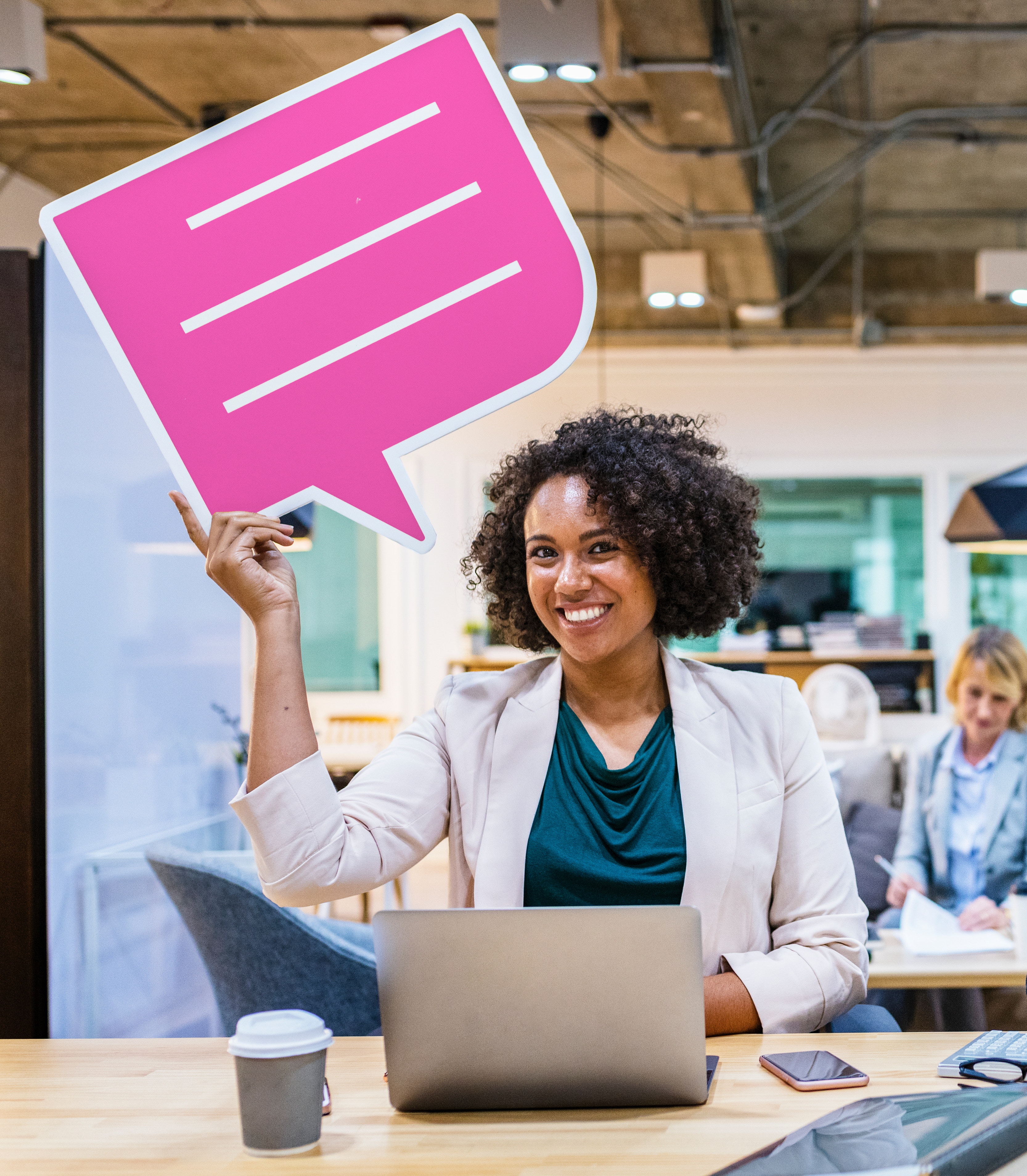 A woman in business casual sits at a desk with an open laptop and holds up a pink cardboard message bubble in her right hand while smiling