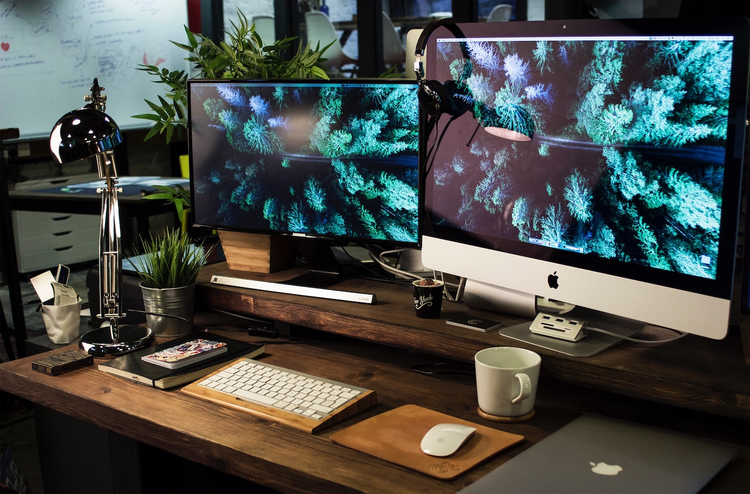 Two computer screens on a wooden desk with a mug