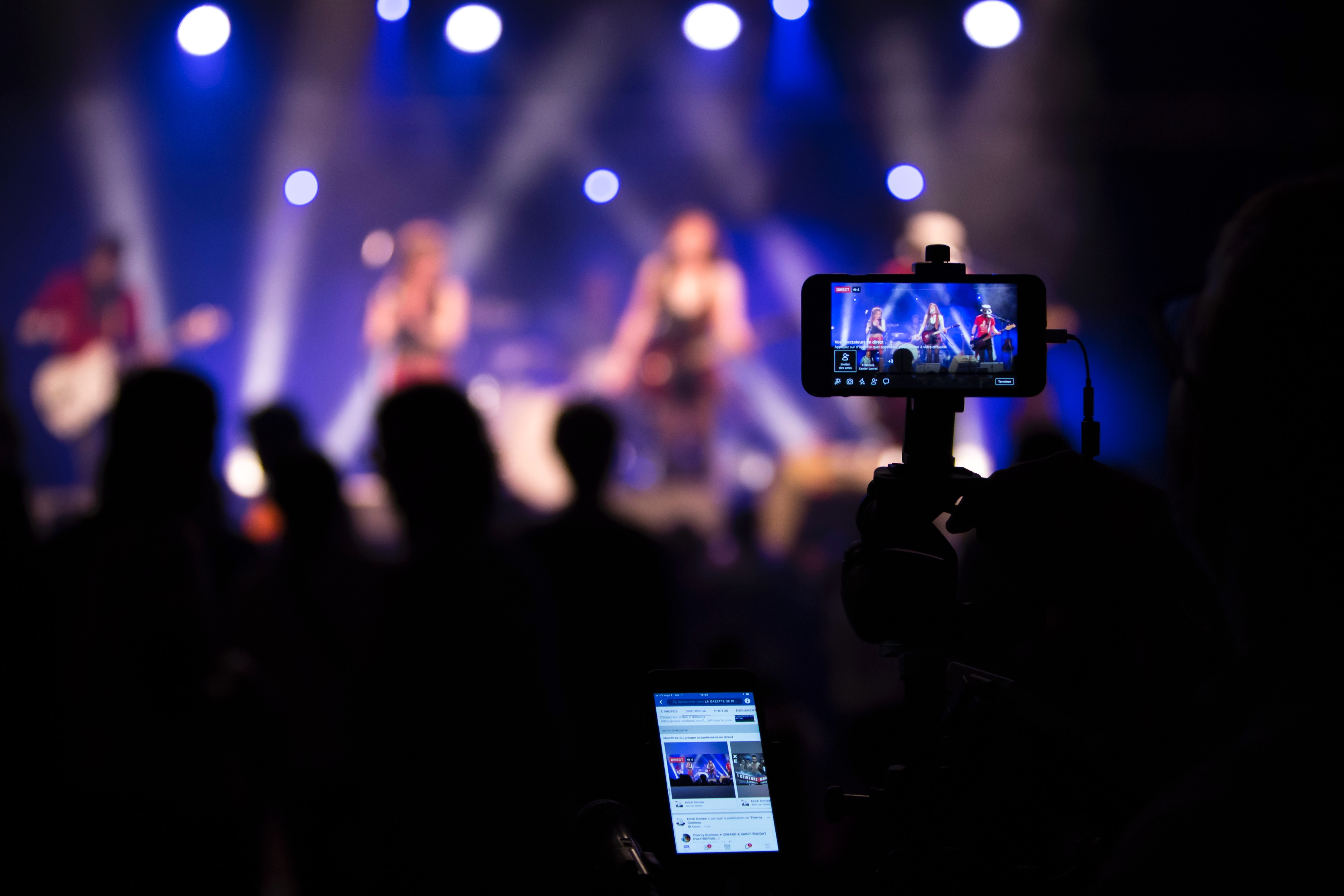 A mounted camera films a concert while someone next to it holds a phone and views the online stream from the camera