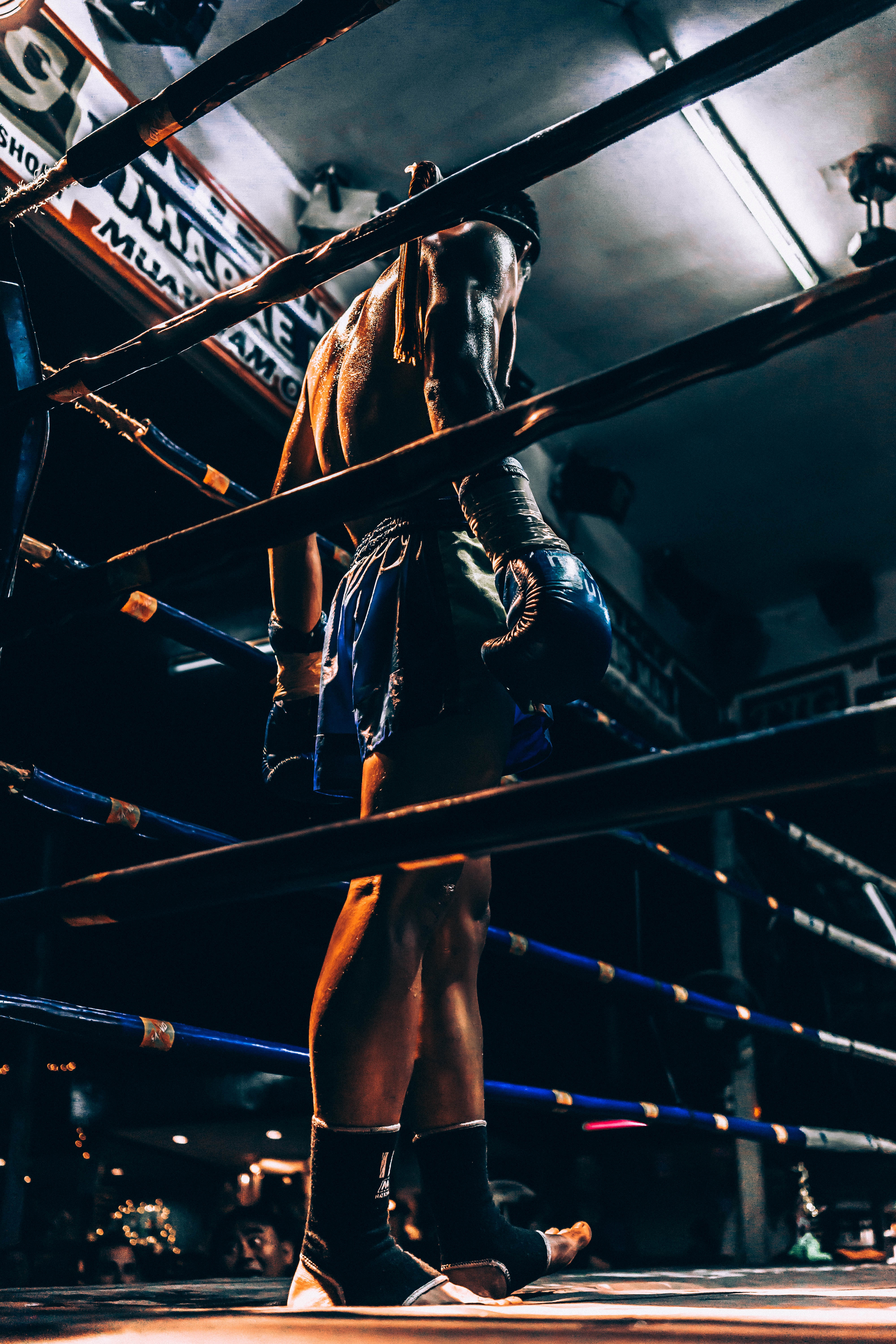 Male boxer stands tall in dark boxing ring